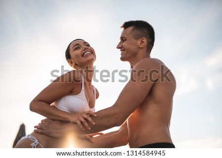 Waist up of the attractive young man standing shirtless and smiling while putting his hands on the waist of beloved woman
