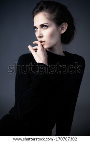 Waist up of young attractive woman with beauty hairstyle, natural make up and hand near her face, wearing black dress and looking up