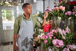 Waist-up photo of a calm multiracial person holding a petal of a flower in a vase with his fingers