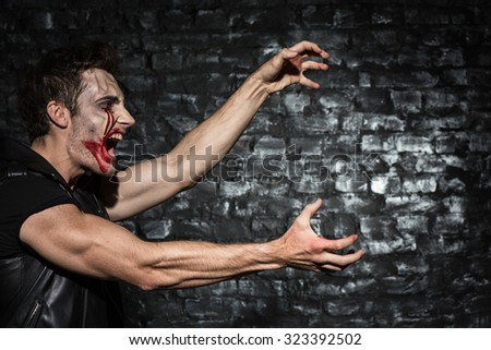Waist up photo of a young man with bloody make up, standing in a profile shouting and stretching his hands to copy place on the black brick wall