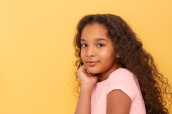 Waist up portrait of a dark skinned young girl with long curly hair wearing pink shirt on a yellow background