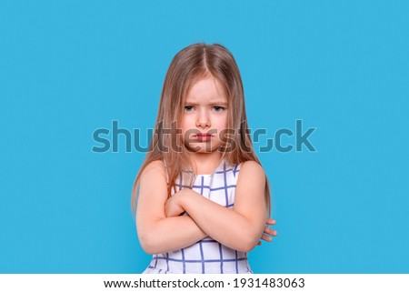 Waist up portrait of a  little  unhappy girl with arms crossed  against blue background with copy space in studio Stock foto ©