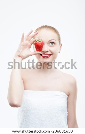 Waist up portrait of a young attractive smiling woman having fun with strawberry, covering her eye, isolated on white