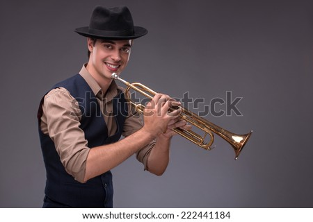 Waist-up portrait of a young handsome Caucasian jazz man in a suit with a black hat looking at the camera holding a trumpet in his hand and playing on it, isolated on grey background with copy place