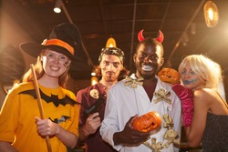 Waist up portrait of adult people wearing Halloween costumes posing as witches and pirates grimacing at camera during party, shot with flash