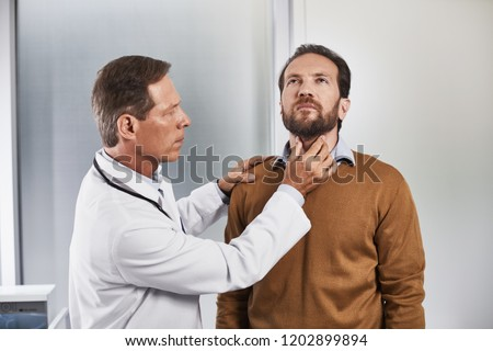 Waist up portrait of adult specialist carefully examining thyroid gland of patient to checking pathology