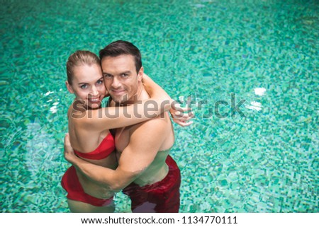 Waist up portrait of affectionate man and woman standing in water in cuddles. They are enjoying rest together in spa center  #1134770111