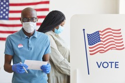Waist up portrait of African-American man standing by voting booth decorated with USA flag and looking at camera on post-pandemic election day, copy space