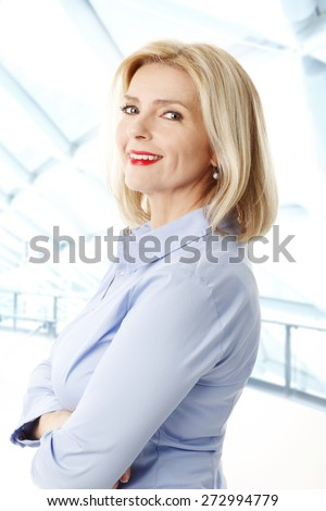 Waist up portrait of beautiful middle age businesswoman standing at office while looking at camera.
