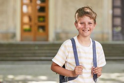 Waist up portrait of blonde schoolboy carrying backpack and smiling at camera while posing outdoors against school building, copy space