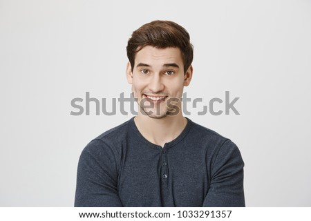 Waist-up portrait of Caucasian handsome attractive young male with dark hair and stubble in casual clothes, pleased to hear praising words from his employer. Positive emotions and face expression