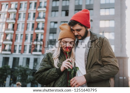 Waist up portrait of charming lady in hat smelling red rose while having romantic date with bearded man