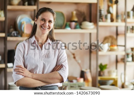 Waist up portrait of cheerful female artisan posing in pottery studio standing with arms crossed, copy space