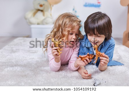 Stock Photo Waist up portrait of cheerful kids involved in funny game. They are lying on the carpet in the nersary