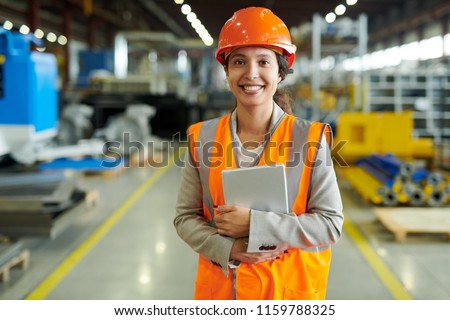 Waist up portrait of cheerful young woman wearing hardhat smiling happily looking at camera while enjoying work in production workshop, copy space #1159788325
