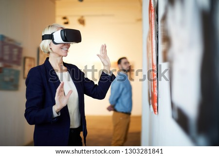 Waist up portrait of contemporary smiling woman wearing VR headset in art gallery, copy space