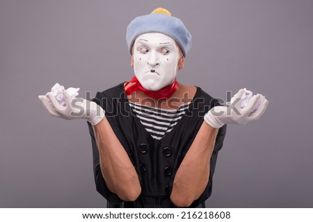 Waist-up portrait of crazy male mime with grey hat and white face holding crumped paper in his hands and looking aside isolated on grey background with copy place