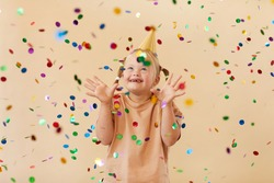 Waist up portrait of excited girl with down syndrome smiling happily while standing under confetti shower in studio, copy space