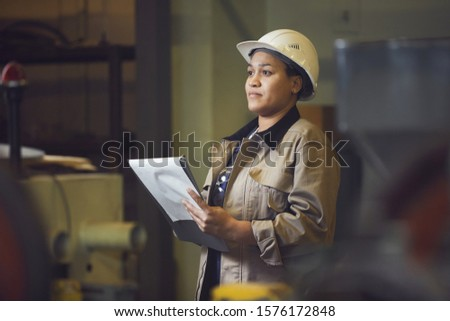 Waist up portrait of female foreman holding clipboard while supervising production at factory, copy space
