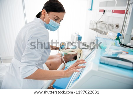 Waist up portrait of female medical worker in protective mask touching monitor of mechanical ventilator. Man lying in hospital bed on blurred background