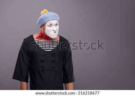 Waist-up portrait of funny male mime with grey hat and white face disappointed looking up and holding his hands omitted down isolated on grey background with copy place