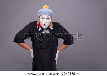 Waist-up portrait of funny male mime with grey hat and white face looking at the camera with great surprise and holding his hands on his waist isolated on grey background