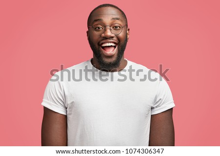 Waist up portrait of glad dark skinned handsome male model with happy expression, wears round spectacles, being in good mood as recieve bonus for diligent work, isolated over pink background #1074306347