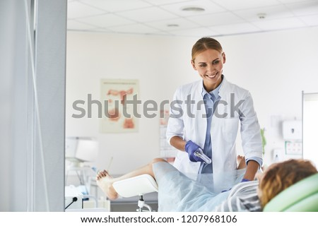 Waist up portrait of gynecologist in white lab coat and sterile gloves using vaginal speculum during pelvic exam. She is looking at patient and smiling