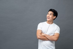 Waist up portrait of handsome cheerful Asian man in arm crossed gesture looking at empty space aside isolated gray background
