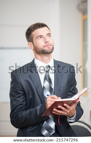 Waist-up portrait of handsome confident businessman sitting at the table and attentively writing some notes in red notebook in office interior and looking up