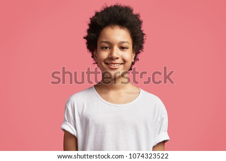 Waist up portrait of handsome smiling black mixed race teenager has Afro hairdo, dressed in casual white t shirt, being in good mood after playing with friends in yard outdoor during Saturday