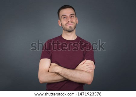 Waist up portrait of handsome young handsome caucasian male with positive expression, has crossed arms, feels happy and confident, wears casual clothes, isolated over gray background.