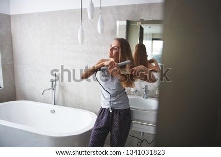 Waist up portrait of happy smiling young woman enjoying of straightening her hair by flat iron while leaning on wash basin in bathroom
