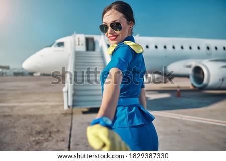 Waist up portrait of joyful beautiful young woman in uniform and sunglasses walking to stairway before flight Stockfoto ©