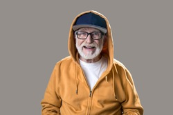 Waist up portrait of joyful elderly man wearing fashionable youth sportswear. He is looking at camera and laughing. Isolated on grey background