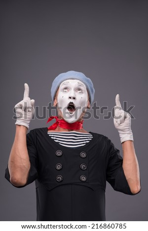 Waist-up portrait of male mime with grey hat and white face funny showing with his fingers and looking up isolated on grey background with copy place