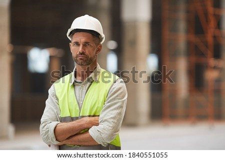 Waist up portrait of mature construction worker looking at camera while standing with arms crossed at construction site, copy space Сток-фото ©