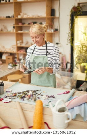 Waist up portrait of mature woman smiling happily while creating flower compositions in art studio, copy space #1336861832