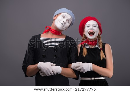 Waist-up portrait of mime couple with white faces, male mime looking at his partner, female mime happy smiling and looking at the camera isolated on grey background with copy place