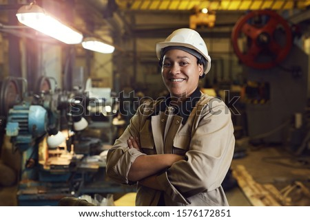 Waist up portrait of mixed-race female worker posing confidently while standing with arms crossed in factory workshop Foto stock ©
