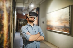 Waist up portrait of modern man wearing VR headset during virtual tour in art gallery or museum, copy space