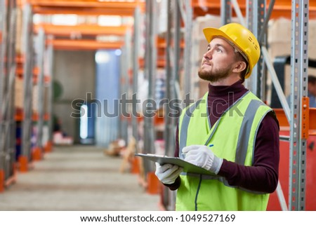 Waist up portrait of modern young man holding clipboard in warehouse looking up at tall shelves, copy space