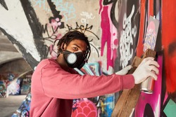 Waist up portrait of multiracial man with dreadlocks wearing respirator painting colored graffiti on public space wall while standing at the stepladder and looking to the camera
