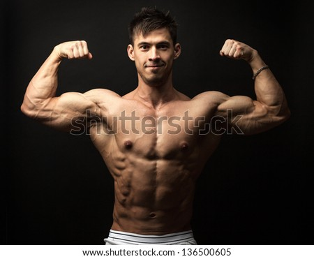 Waist-up portrait of muscular man flexing his biceps against black background