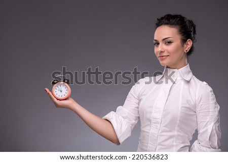 Waist-up portrait of pretty girl with surprised face holding an alarm clock in her hand and looking at it with opened mouth showing at a clock, with copy place isolated on grey background