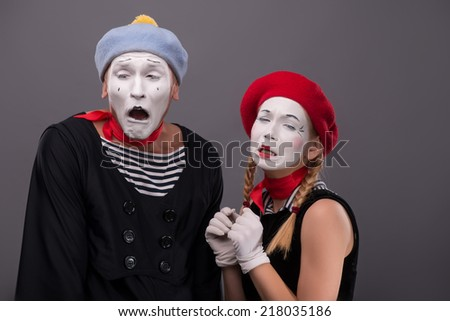 Waist-up portrait of sad mime couple crying with closed eyes, female mime touching her braid isolated on grey background with copy place