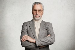 Waist up portrait of serious bearded mature man keeps arms folded, dressed in formal suit, confident in his knowledge, isolated on white concrete background. Company director comes on business meeting