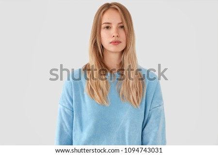 Waist up portrait of serious good looking blonde female in loose light blue casual sweater, looks attentively and pensively at camera, enjoys domestic atmosphere, isolated on white concrete wall