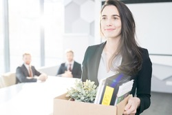 Waist up portrait of smiling young businesswoman holding box of personal belongings  leaving office after quitting job, copy space