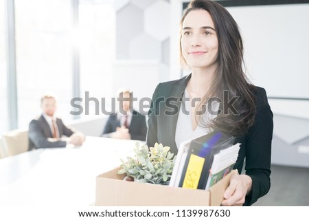 Photo of  Waist up portrait of smiling young businesswoman holding box of personal belongings  leaving office after quitting job, copy space